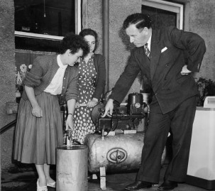 Male demonstrator and two interested housewives, c1950s